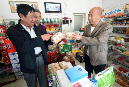 在霸州市南夹河村,乡村食品药品协管员(左)到超市检查出售的食品。(资料片)新华社记者李晓果摄