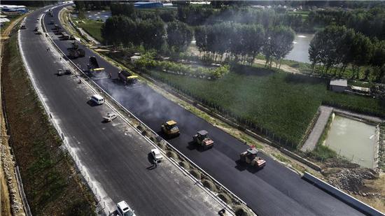 8月29日,在京秦高速河北遵化段建设工地,工人进行铺设路面作业(无人机拍摄)。