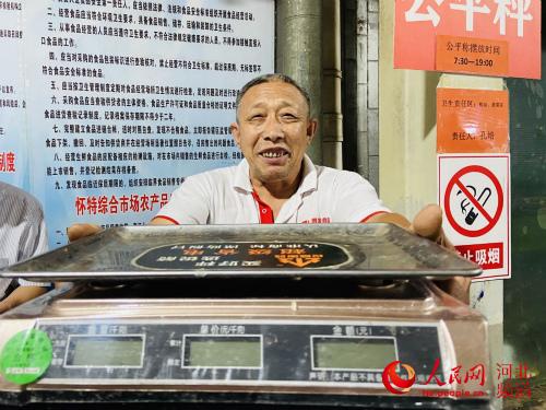 河北省石家庄市怀特综合市场内的商家在展示自家贴有绿色合格标志的数字指示称。 付兆飒摄