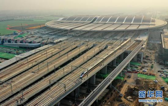 12月26日,用于测试的动车组列车驶离京雄城际铁路雄安站(无人机照片)。新华社记者 牟宇 摄