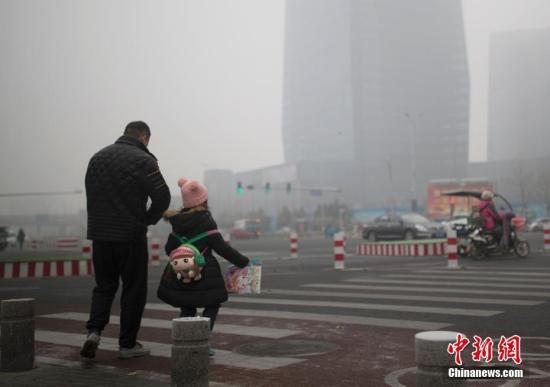 资料图:北京市民在雾霾中出行。中新社记者 刘关关 摄