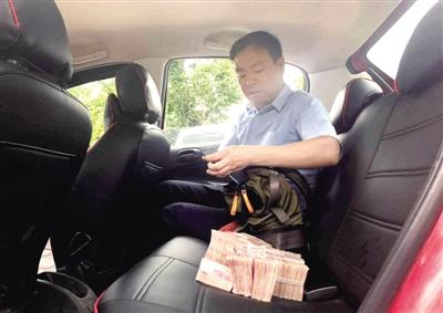 郑州男子开车发现车内多了个包 内装3大捆百元大钞
