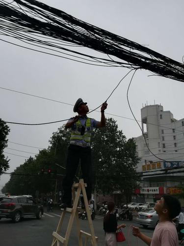 郑州早高峰电缆垂落 协警双手托举保道路畅通