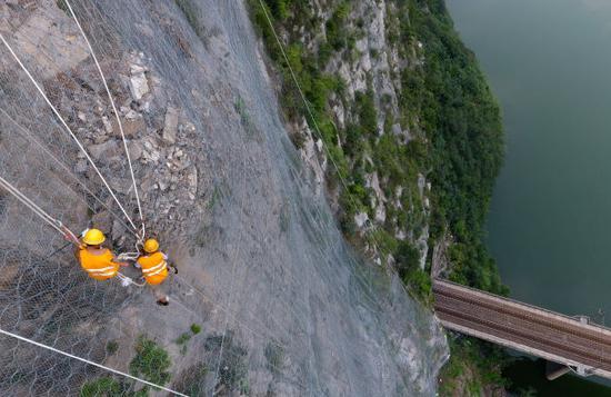 8月9日,抢险人员在侯月铁路柏枝隧道上方悬崖进行碎石作业(无人机拍摄)。