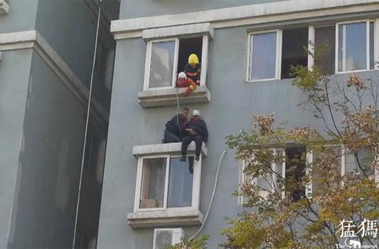 郑州七旬老人悬坐窗台 被众人齐