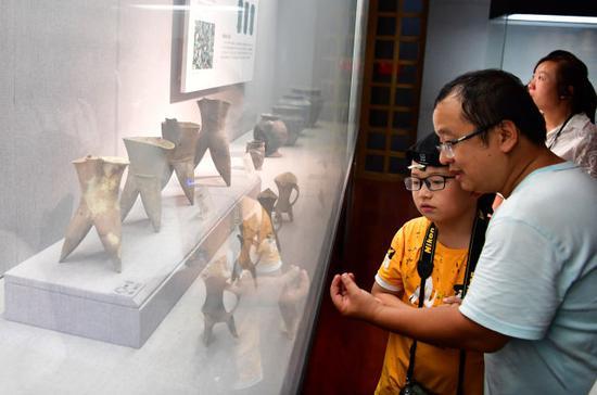 8月14日,在河南洛阳博物馆,一名家长在给小朋友介绍展品。