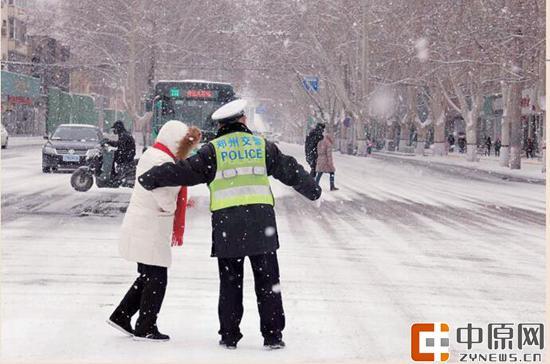昨日一名交警雪中护送行人过路口 记者 张玉东 通讯员 邢红军 李霞 图