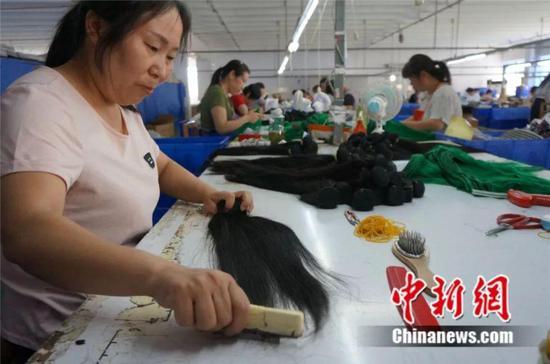 工人在发制品工厂里生产假发 韩章云 摄