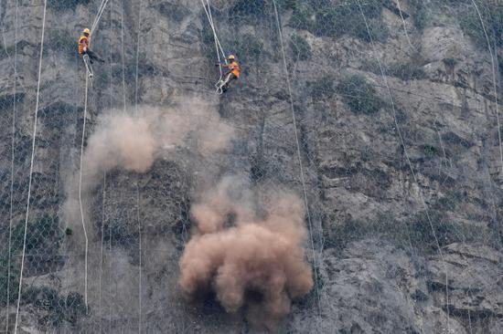 8月9日,抢险人员在侯月铁路柏枝隧道上方悬崖进行碎石作业。
