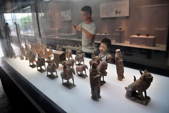 8月14日,在河南洛阳博物馆,一名小朋友在欣赏展品。