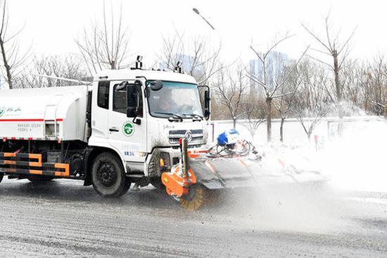 2月10日,郑州环卫工作人员清理路面积雪。
