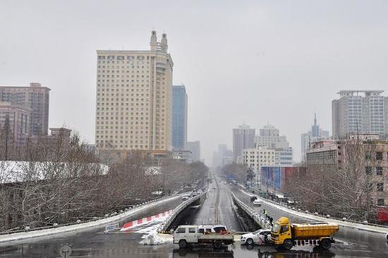 2月10日,郑州市政部门清理路面积雪。