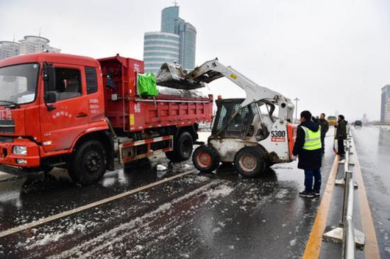 2月10日,郑州市政部门工作人员清理路面积雪。