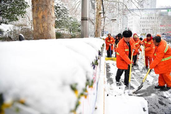 2月10日,环卫工人清除路面积雪。