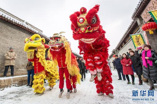 2019年2月10日,游客在河南安阳市文峰区仓巷街观看民间艺术舞狮表演。