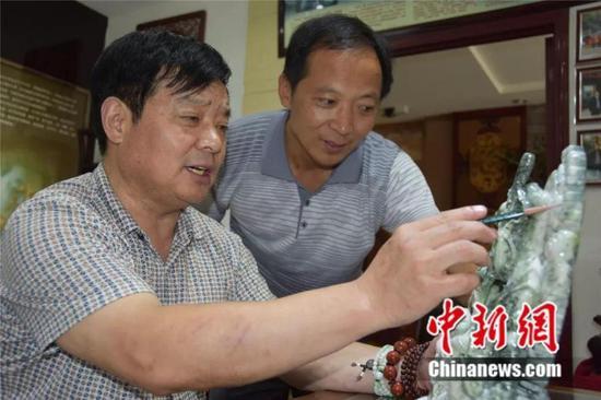图为石佛寺镇玉雕匠人探讨玉雕设计 镇平县委宣传部供图