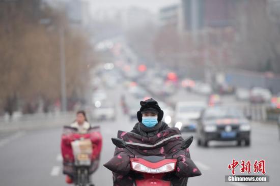 资料图:山西省临汾市,市民戴口罩出行。中新社记者 韦亮 摄