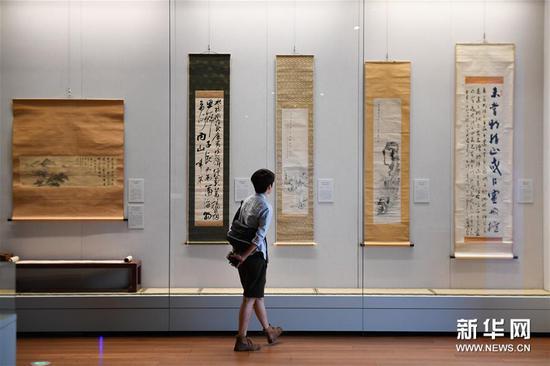 """9月18日,观众在浙江大学艺术与考古博物馆参观""""中国与世界""""——新获藏品展。该展览展出的是浙江大学2009年迄今新获的部分藏品。展品来源于捐赠及购藏,内容涉及书画、碑刻、瓷器、漆器、金铜造像等。 新华社记者 黄宗治 摄"""