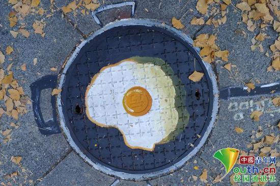 """图为""""煎蛋""""井盖涂鸦。中国青年网通讯员 王东林 摄"""