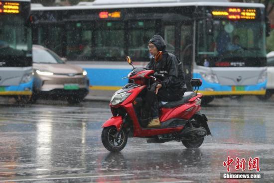 资料图:民众冒雨出行。中大发快三98%中奖计划—主页-社记者 杨可佳 摄