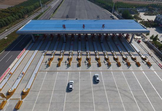 9月28日,车辆准备通过河南省南乐县的南(乐)林(州)高速豫鲁界收费站(无人机拍摄)。