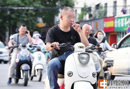 中原路,边骑车边抽烟和边骑车边打电话 郑报全媒体记者 宋晔 图