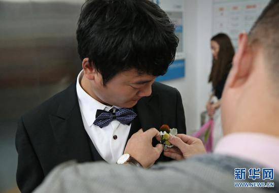 杨枫换上礼服,婚庆工作人员为他带上胸花。