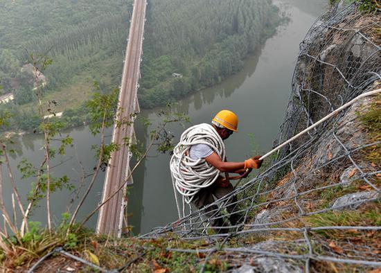 8月9日,抢险人员从侯月铁路柏枝隧道上方山顶垂降,准备进行碎石作业。