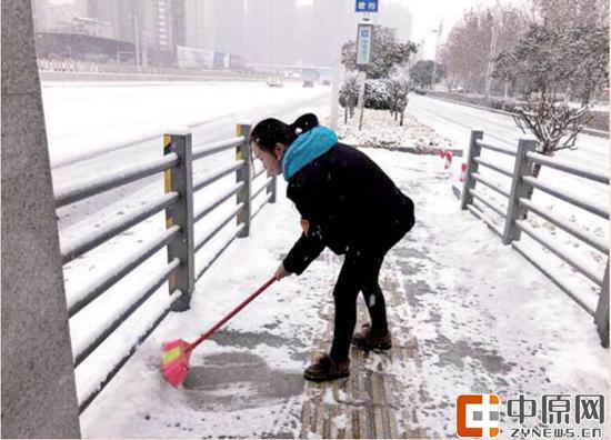 郑州快速公交工作人员清理站台积雪(记者 张华 通讯员 张伟 图)