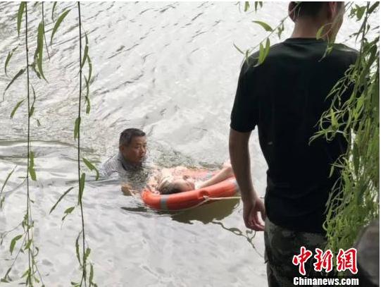 图为金诚老师正在河中救人。