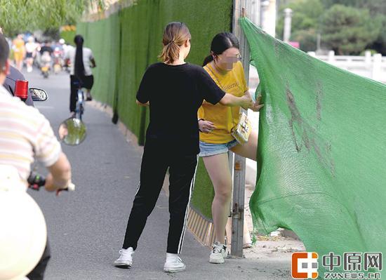 7月1日下午,花园路与东风渠交叉口,一女子从围挡缝隙穿过 郑报全媒体记者 周甬 图