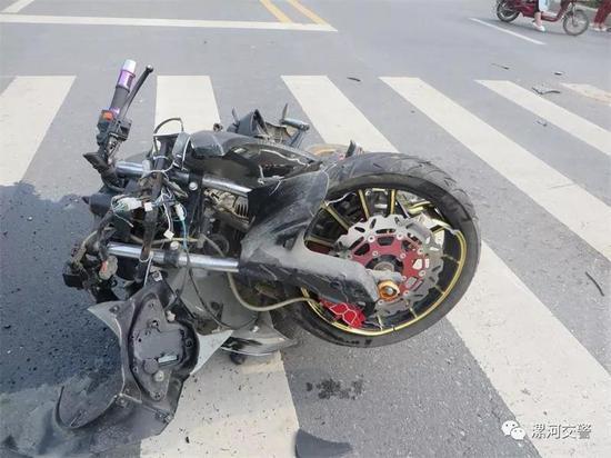 两轮摩托车受损严重,路面散落着很多碎片。