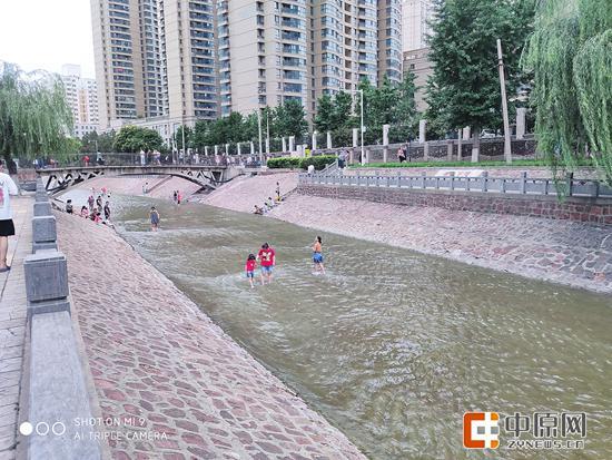 不顾河边的安全警示牌,还有家长带孩子在金水河玩水 郑报全媒体记者 徐富盈 图
