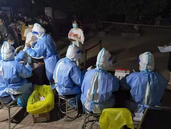 郑州:身着防护服 他们冒酷暑奋战在各个社区(图)