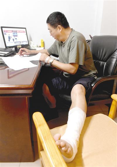 9日下午,尹玉东在办公室讲述事发情况,他左腿包扎着纱布。