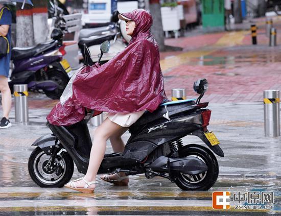 昨天,市民身披雨衣骑行在雨中