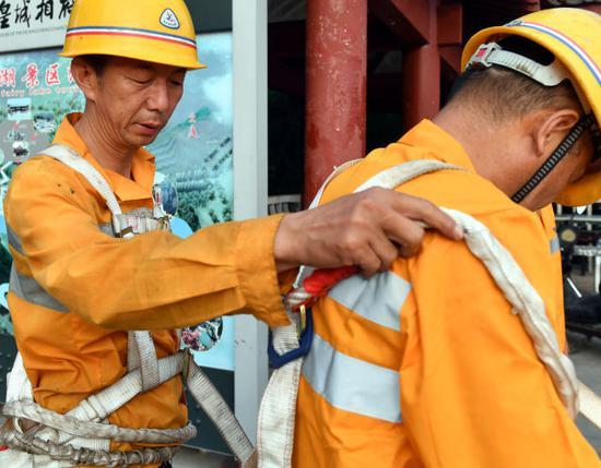 8月9日,抢险小组组长马建宏(左)为同事检查安全绳捆绑情况。