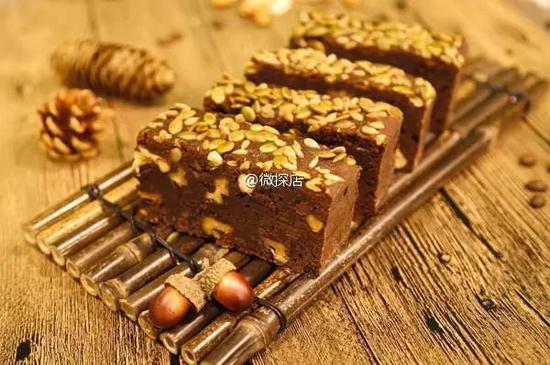 经典之作布朗尼蛋糕,它既有乳脂软糖的甜腻,又有蛋糕的松软,中间夹着大量的腰果杏仁,铺上淡绿色的南瓜子,可可味浓郁!