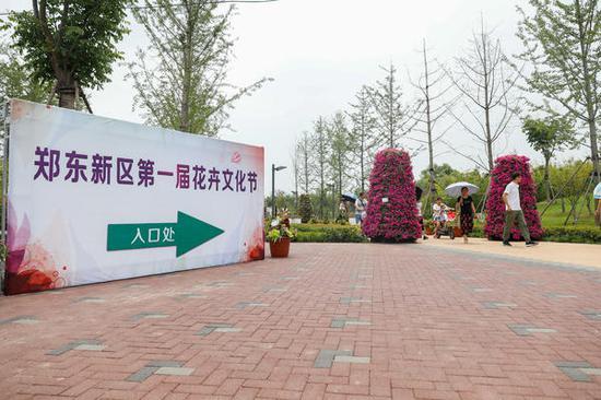 花卉文化节入口处,虽然烈日炎炎但前来赏花的人们热情不减。