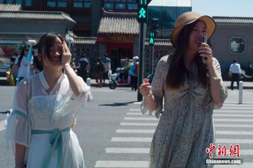 5月21日,北京天气晴晒,两位姑娘走过人行横道。中新社记者 盛佳鹏 摄