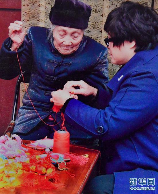 母亲手把手教李水琴制作香包。(资料图片)