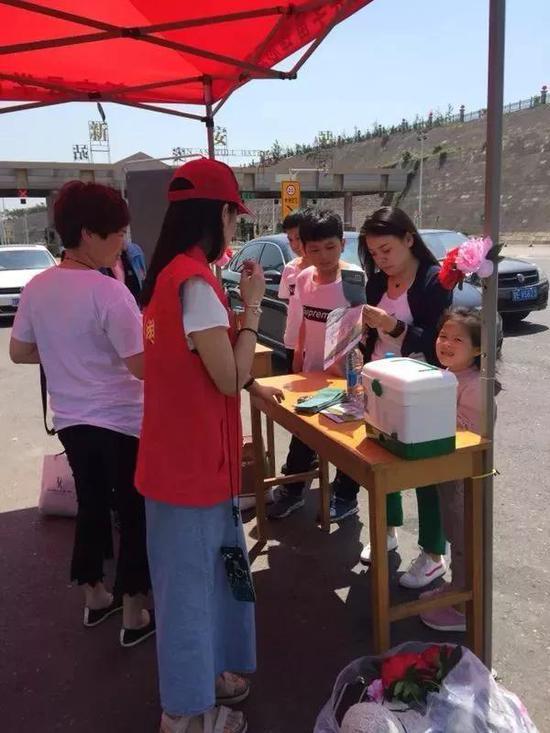 旅游志愿者为来洛游客提供咨询服务。