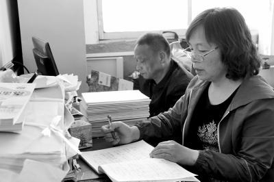 温培红在办公室改作业,丈夫在一旁看书。