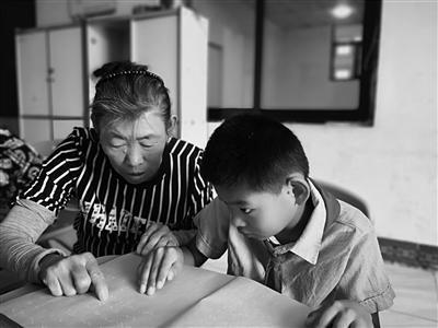 刘瑞侠教孙子认盲文。