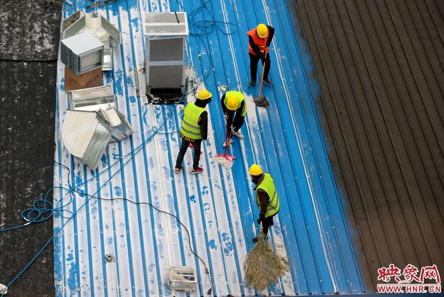工人师傅清理屋顶的积雪便于后续施工