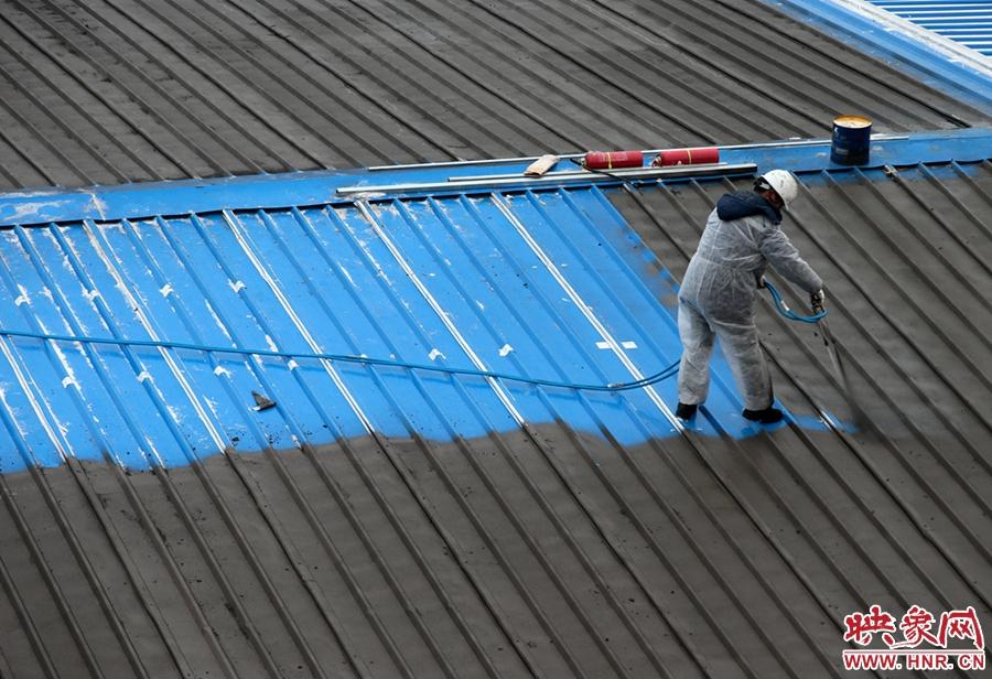 一位工人正在病房区屋顶进行喷涂