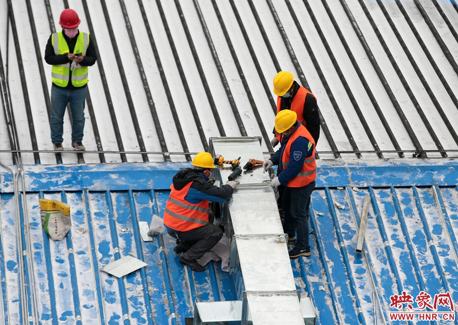 在屋顶安装通风管道的工人