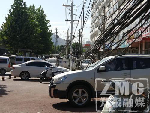 两根电线杆被撞断,十来根电缆垂下来……三个月了,小区居民不知找谁来处理。