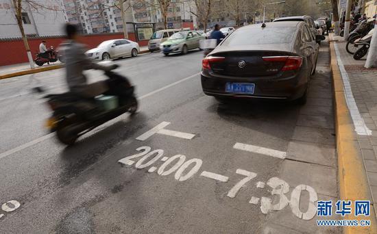 3月22日,郑州市金水区经八路,一市民骑车经过一个限时免费停车位。