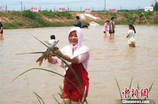 成功摸到大鲤鱼让参与者开心不已 韩章云 摄